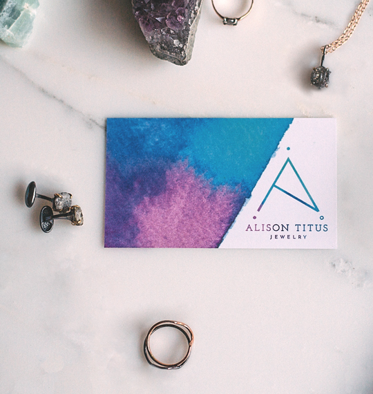 Alison Titus Jewelry business card on tabletop next to jewelry product